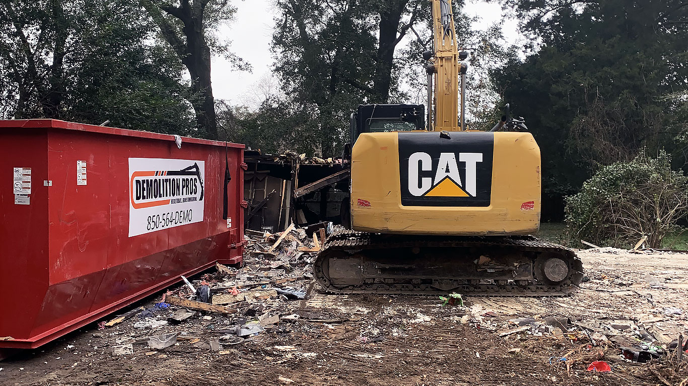 A Demolition Pros dumpster and equipment on a job site